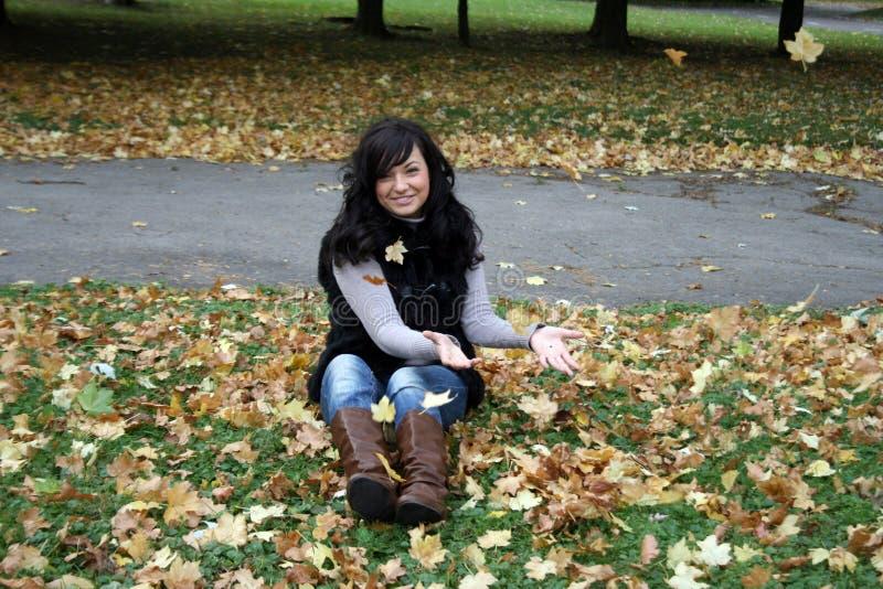 Werfende Blätter der recht jungen Frau lizenzfreies stockfoto