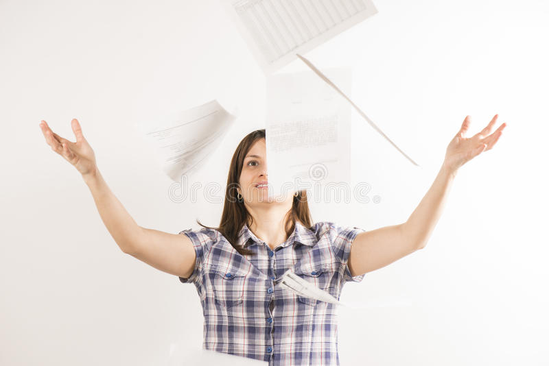 Werfende Blätter Papier der jungen Frau in der Luft lizenzfreie stockfotografie