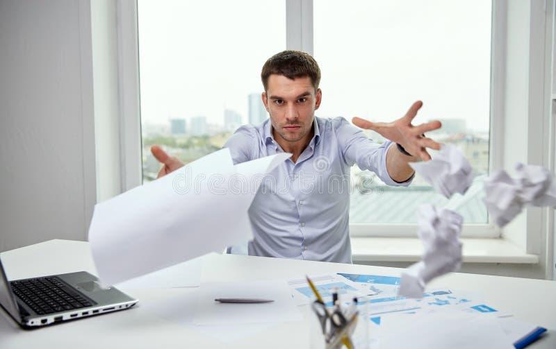 Werfende Papiere des verärgerten Geschäftsmannes im Büro stockfotos
