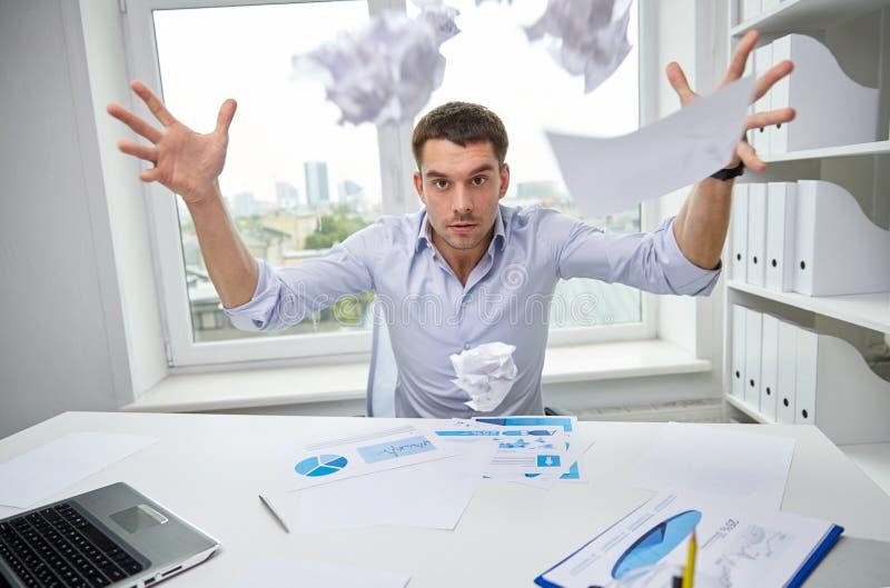 Werfende Papiere des verärgerten Geschäftsmannes im Büro lizenzfreies stockfoto