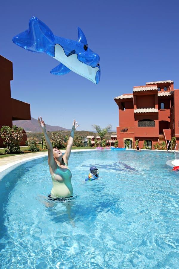 Werfender aufblasbarer Delphin des Spielzeugs der Frau in einer Luft stockfoto