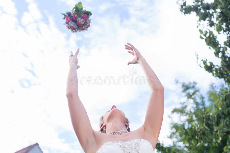 Werfender Blumenblumenstrauß der Braut an der Hochzeit lizenzfreie stockfotografie