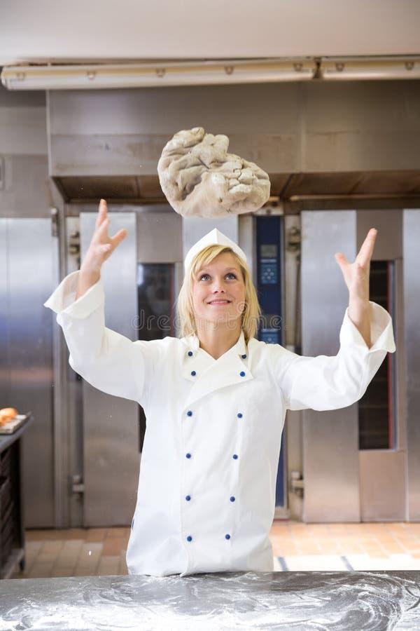 Werfender Brotteig des Bäckers in der Bäckerei oder im Backhaus lizenzfreie stockbilder