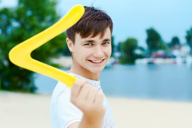 Werfender Bumerang des jungen Mannes T?tigkeiten des Sommers im Freien stockbild