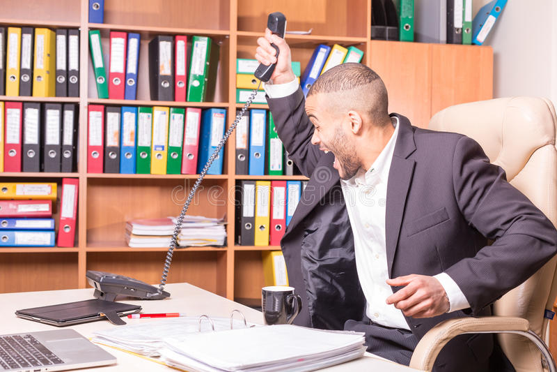 Werfender Hörer des afrikanischen Mannes nach unangenehmem Anruf stockbilder