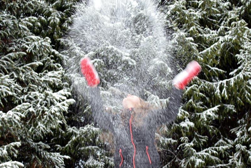 Werfender Schnee der jungen Frau in der Luft lizenzfreie stockfotografie