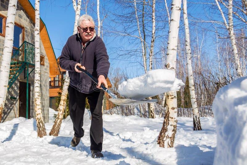Werfender Schnee des älteren Mannes mit Schaufel vom Privathausyard im Winter am hellen sonnigen Tag Ältere Person, die Schnee im stockbild