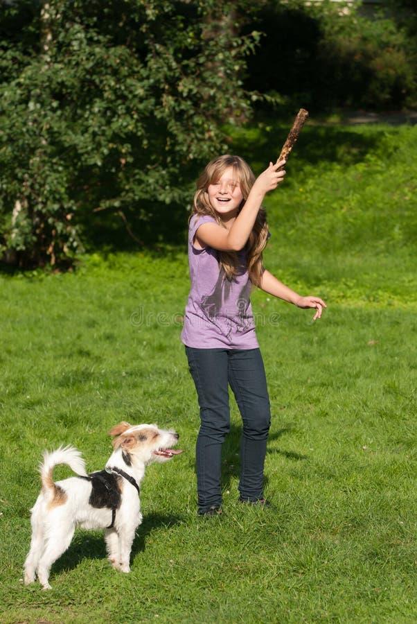 Werfender Steuerknüppel des Mädchens für Hund lizenzfreie stockfotografie