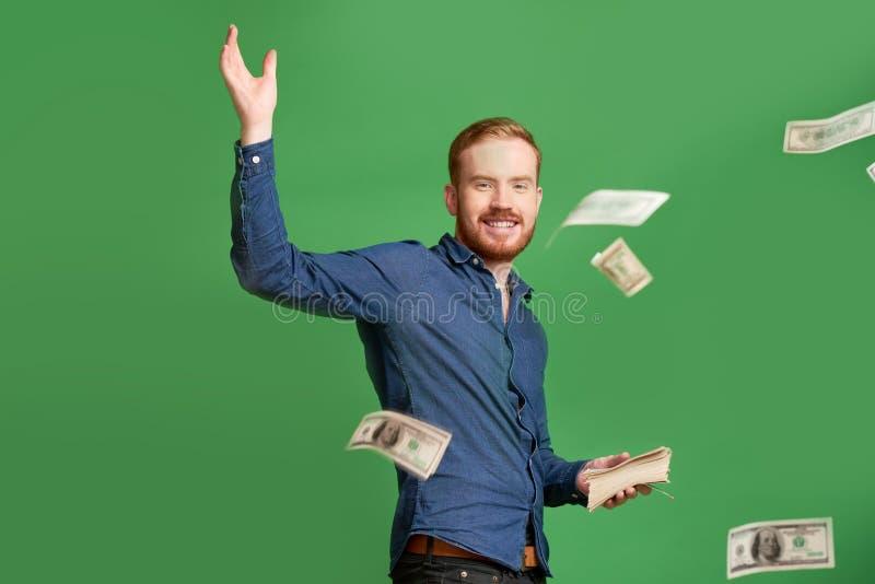 Werfendes Geld des jungen Mannes lizenzfreies stockfoto