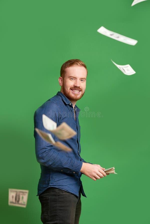 Werfendes Geld des Reichers lizenzfreie stockfotografie