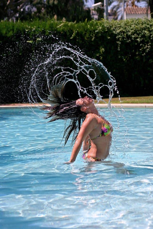 Werfendes Haar des Mädchens rückseitig schnell im sonnigen, blauen Swimmingpool stockbild