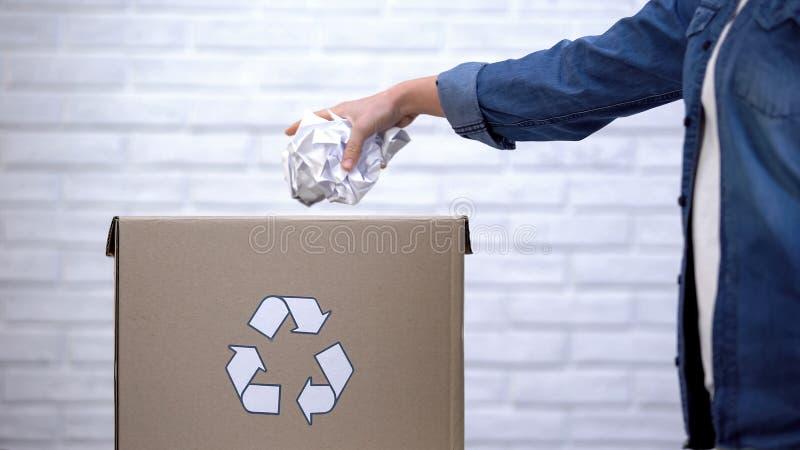 Werfendes Papier der Person in Abfalleimer, überschüssiges sortierendes Konzept, Wiederverwertungssystem lizenzfreies stockbild