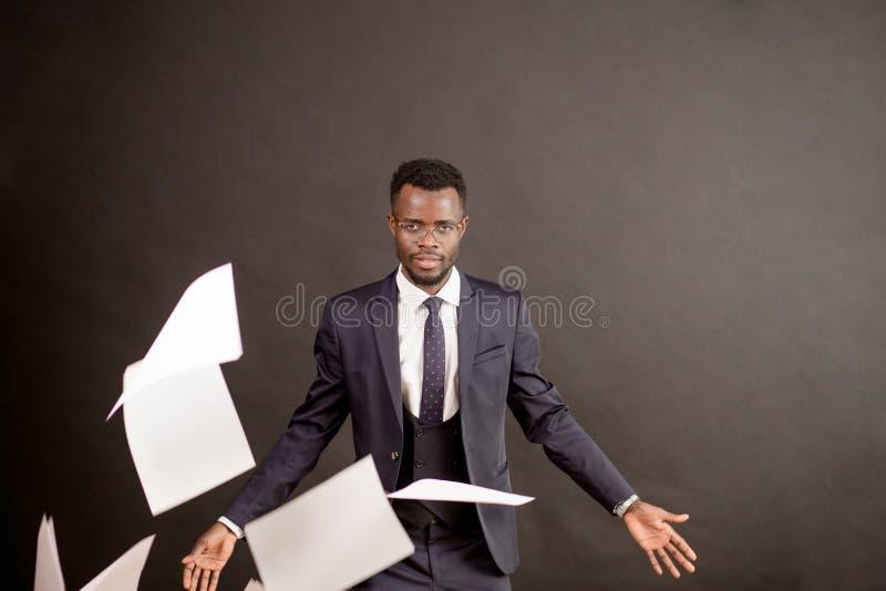 Werfendes Papier des eleganten Geschäftsmannes auf einem schwarzen Hintergrund lizenzfreies stockfoto