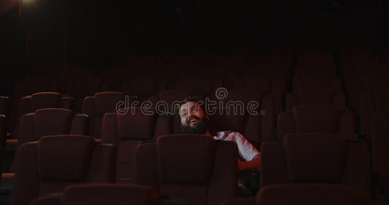Werfendes Popcorn des unhöflichen Kinogängers im Kinoauditorium lizenzfreie stockbilder