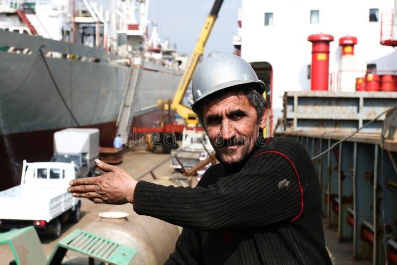 Werftarbeitskraft, die etwas zeigt stockfotografie