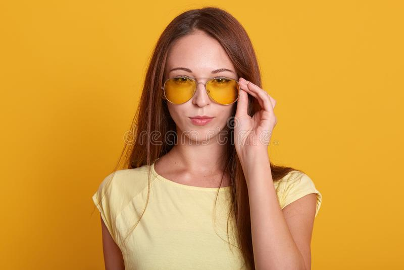 wering偶然成套装备的可爱的妇女水平的射击,保留在她时髦的太阳镜的手,有黑暗的长的直发, 免版税库存图片