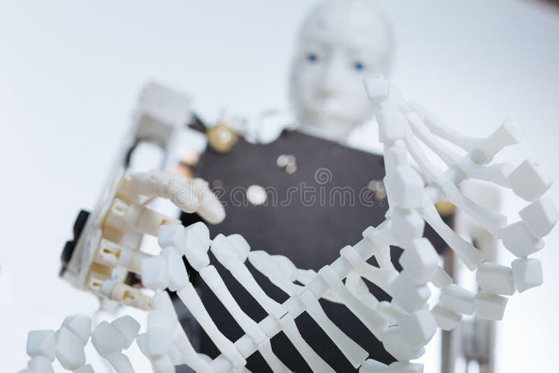 Werk robot uit houdend een plastic model van het genoom stock afbeeldingen
