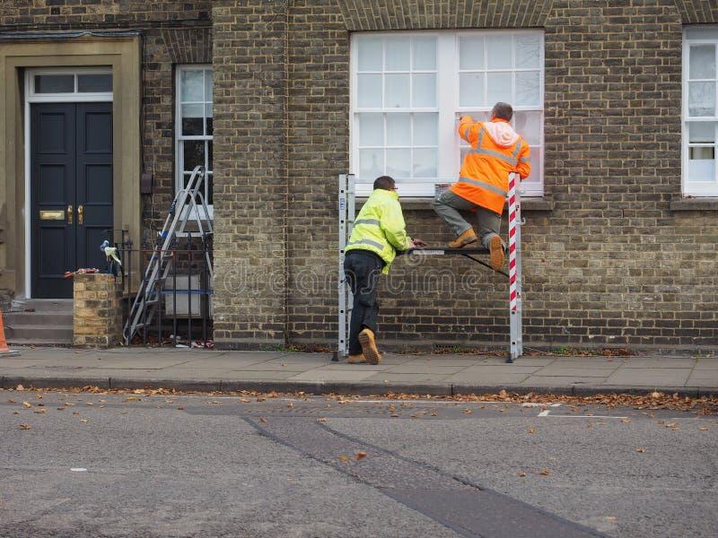 werk in uitvoering die een venster in Cambridge schilderen stock foto