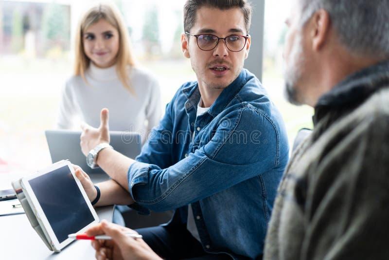 Werkdag Groep jonge moderne mensen die in slimme vrijetijdskleding zaken bespreken terwijl het werken in het creatieve bureau stock foto