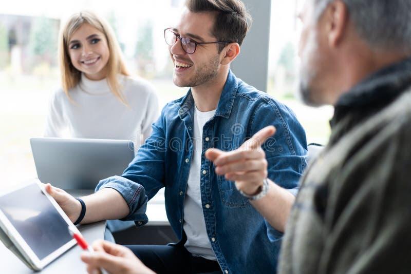 Werkdag Groep jonge moderne mensen die in slimme vrijetijdskleding zaken bespreken terwijl het werken in het creatieve bureau stock afbeelding