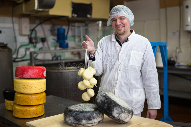 Werkend bij de productie van kaas bij zuivelfabriek, met kazen royalty-vrije stock foto's