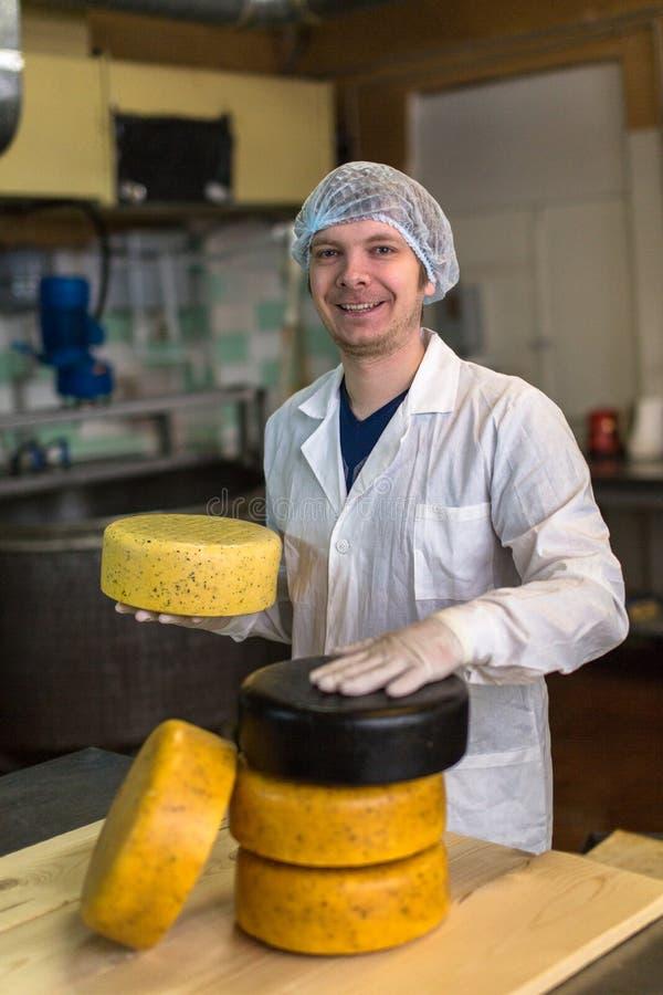 Werkend bij de productie van kaas bij zuivelfabriek, met kazen royalty-vrije stock foto