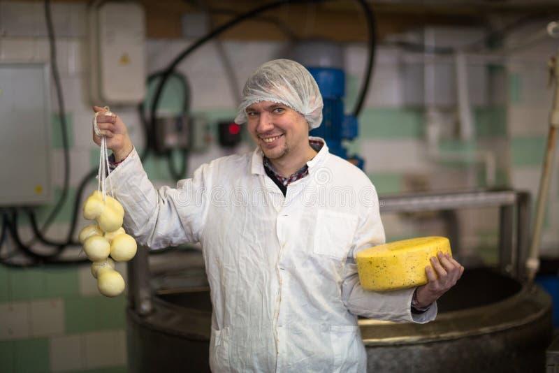 Werkend bij de productie van kaas bij zuivelfabriek, met kazen stock foto's
