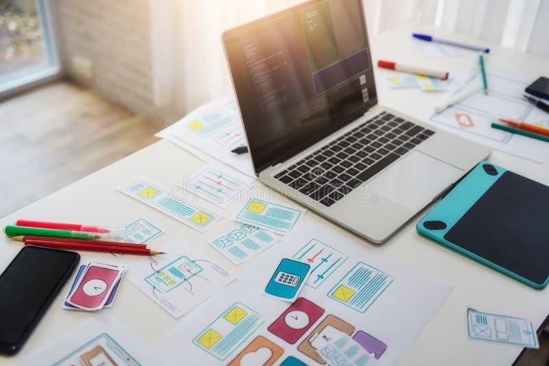 Werkend bureau die van programmeur technologieën mobiele telefoon met schetstoepassing ontwikkelen op lijst Het concept van de ge stock fotografie
