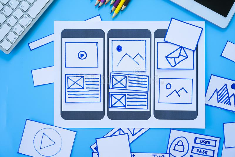 Werkend bureau met handen die wireframe de schermen van mobiele ontvankelijke website sorteren Het ontwikkelen van wireframe het  royalty-vrije stock afbeelding