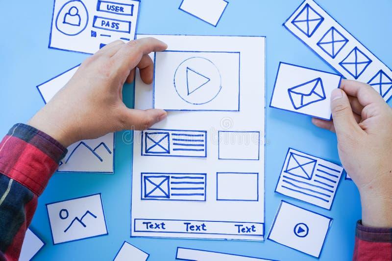 Werkend bureau met handen die wireframe de schermen van mobiele ontvankelijke website sorteren Het ontwikkelen van wireframe het  stock foto