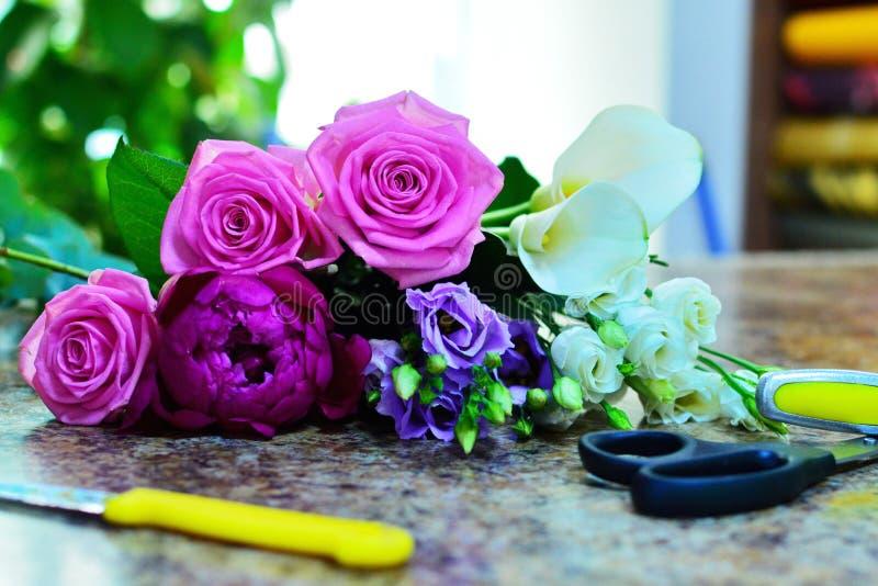 Werkend hulpmiddel van de bloemist in de bloemwinkel stock afbeelding