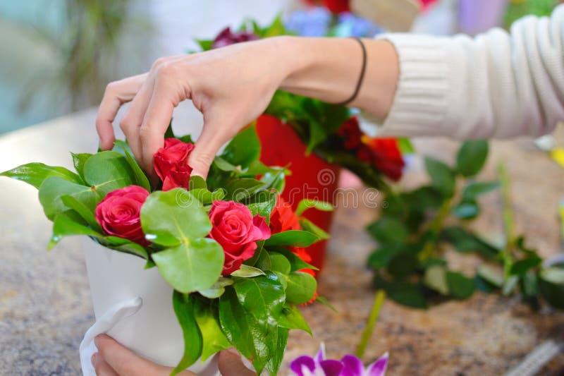 Werkend hulpmiddel van de bloemist in de bloemwinkel royalty-vrije stock foto