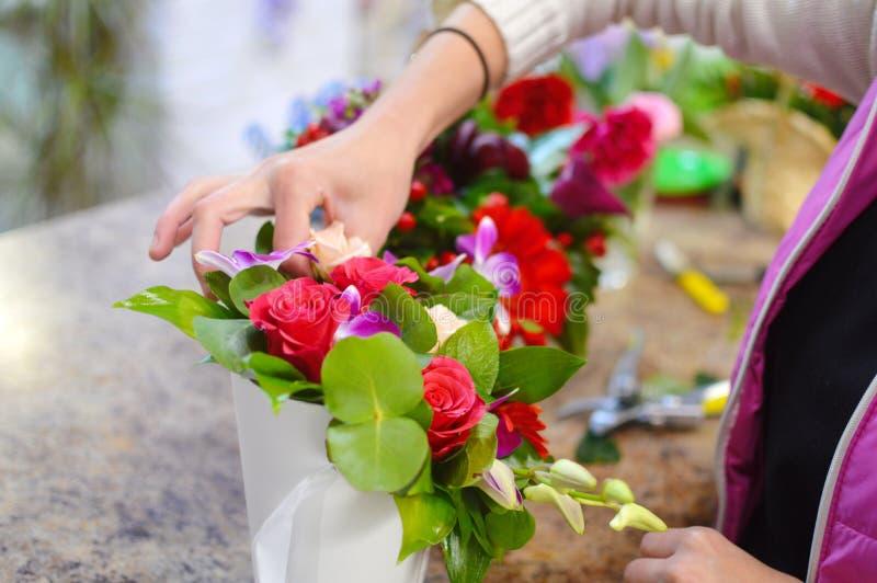 Werkend hulpmiddel van de bloemist in de bloemwinkel stock afbeeldingen