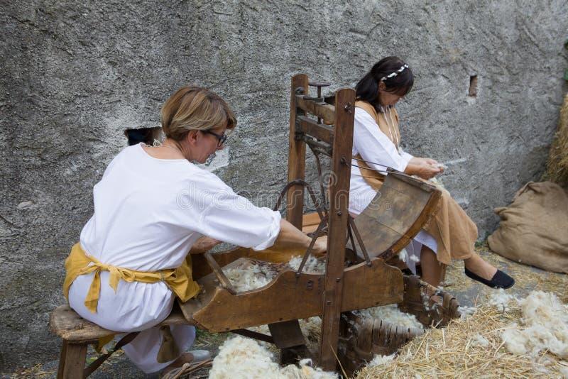 Werkend met een origineel middeleeuws weefgetouw twee vrouwelijke werknemers die garen van wol maken royalty-vrije stock foto