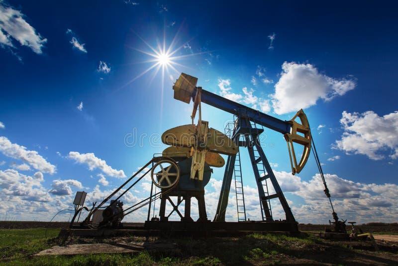 Werkende die olie en gasput op zonnige hemel wordt geprofileerd royalty-vrije stock fotografie