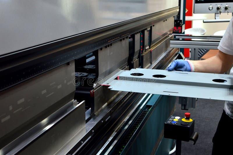 Werkende exploitant bij een buigend het bladmetaal van de productieinstallatie op een blad buigende machine stock afbeelding
