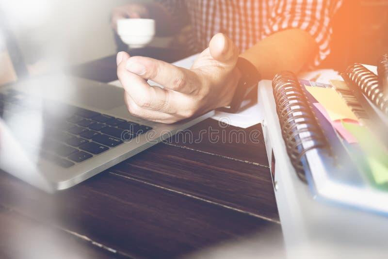 Werkende gebruikt laptop van de zakenmanhand op houten bureau, begeleidt artikel in financiën stock afbeelding