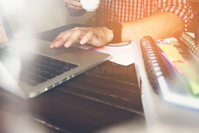 Werkende gebruikt laptop van de zakenmanhand op houten bureau, begeleidt artikel in financiën Uitstekend Effect stock foto