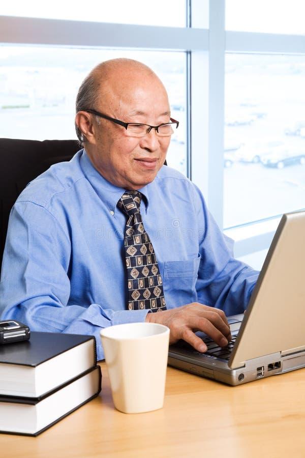 Werkende hogere Aziatische zakenman stock afbeelding
