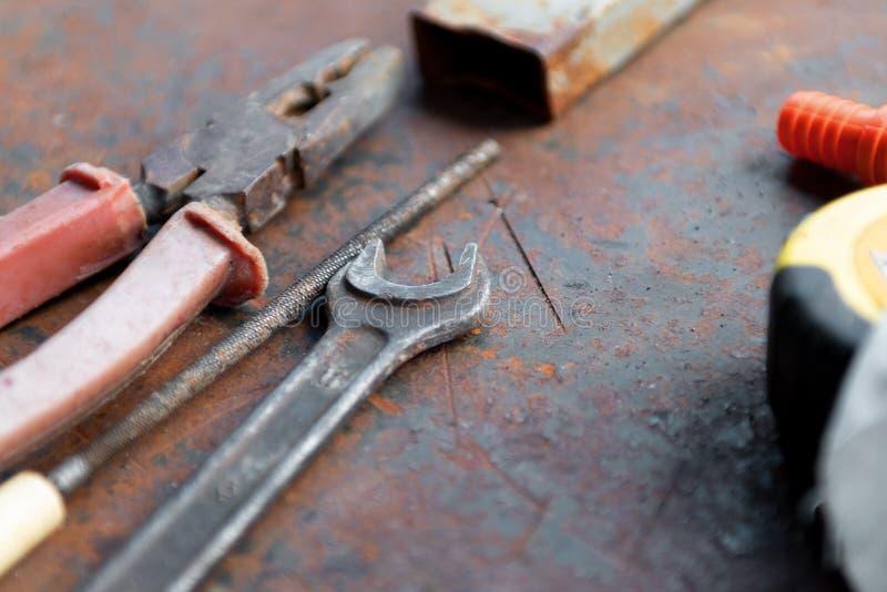 Werkende hulpmiddelen op een vuile ruwe werkbank stock fotografie