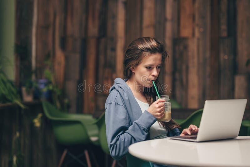 Werkende jonge vrouw met laptop stock foto