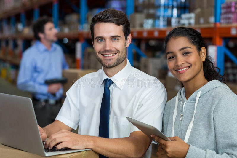 Werkende laptop van de pakhuisarbeider en digitale tablet royalty-vrije stock afbeelding