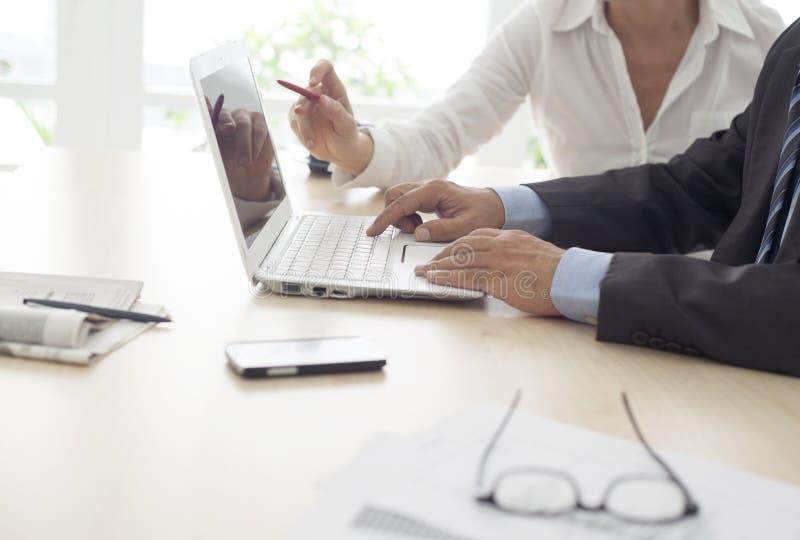 Werkende man en vrouw in het bureau stock fotografie