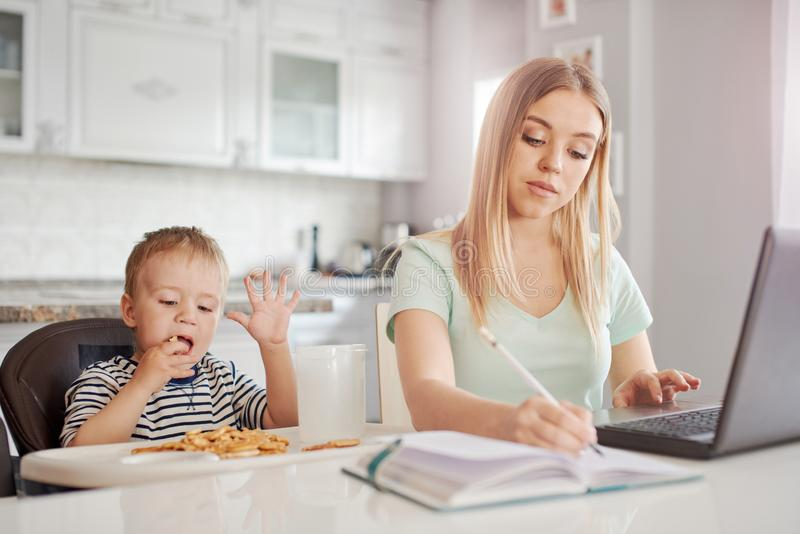 Werkende moeder met kind in de keuken royalty-vrije stock fotografie