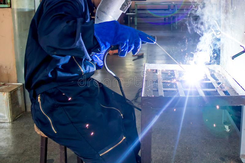 Werkende persoon over het lassenmachine van het lassersstaal stock afbeelding