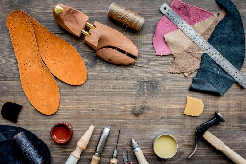 Werkende plaats van schoenmaker Huid en hulpmiddelen op bruine houten bureau hoogste mening als achtergrond copypace stock fotografie