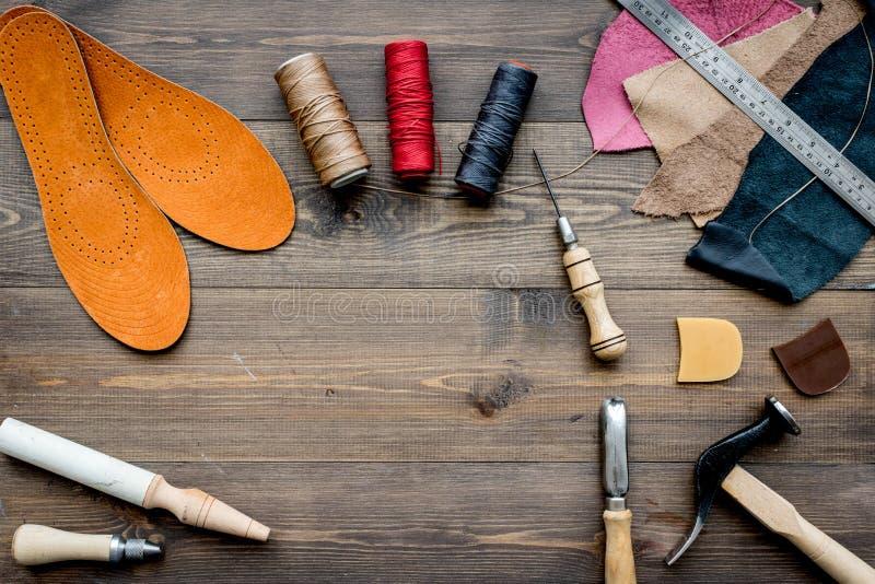 Werkende plaats van schoenmaker Huid en hulpmiddelen op bruine houten bureau hoogste mening als achtergrond copypace royalty-vrije stock afbeeldingen