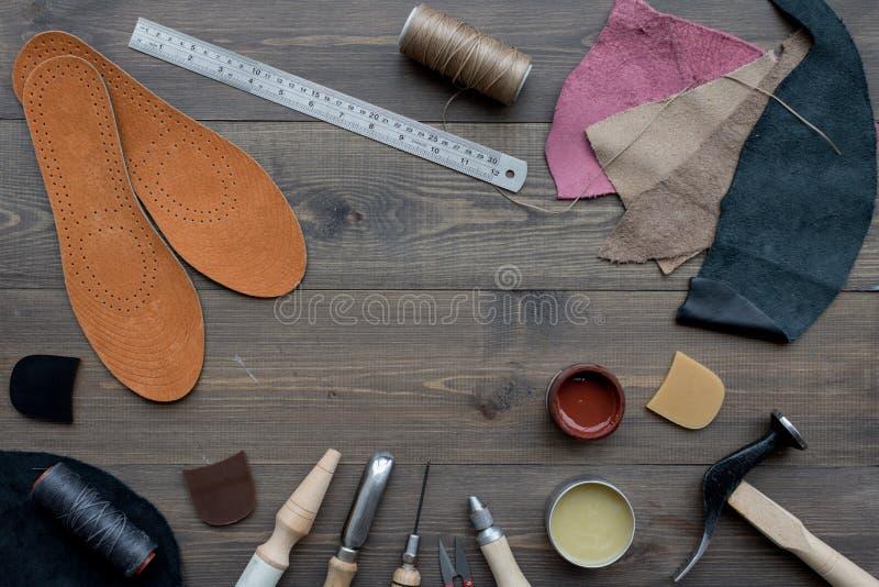 Werkende plaats van schoenmaker Huid en hulpmiddelen op bruine houten bureau hoogste mening als achtergrond copypace royalty-vrije stock fotografie