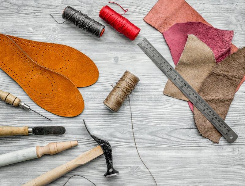 Werkende plaats van schoenmaker Huid en hulpmiddelen op grijze houten bureau hoogste mening als achtergrond stock afbeelding