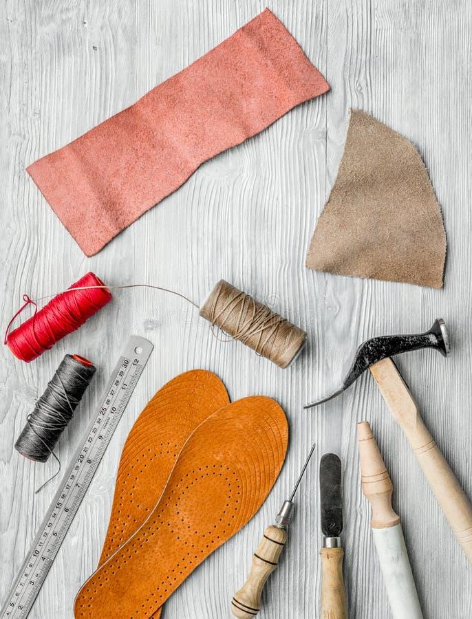 Werkende plaats van schoenmaker Huid en hulpmiddelen op grijze houten bureau hoogste mening als achtergrond royalty-vrije stock foto